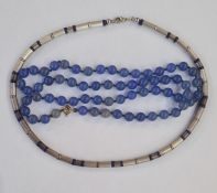 Bead necklace of tubular silver coloured beads interspaced by lapis lazuli beads and a string of