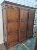 20th century oak three-door wardrobe with cavetto moulded cornice above the panelled doors, with