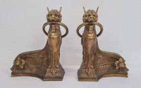 Empire style gilt bronze chenets each in the form of sphinx with ring in mouth and on sweeping