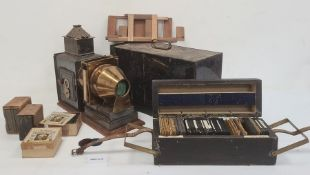 Antique brass black japanned metal magic lantern in metal carrying case and large quantity of
