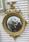 Reproduction circular mirror surmounted by eagle amongst acorns, convex plate in ball decorated