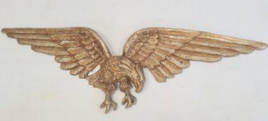 Gilt metal spread-eagle wall plaque, 109cm wide
