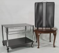 Modern two-tier low hostess trolley / tv stand on castors in black and chrome, a circular coffee