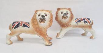 Pair of Staffordshire-style pottery lions painted with Union Jacks, 25cm high x 32cm long (2)