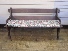 Dark wood benchwith floral cushion and similar oval slatted coffee/occasional table, on straight