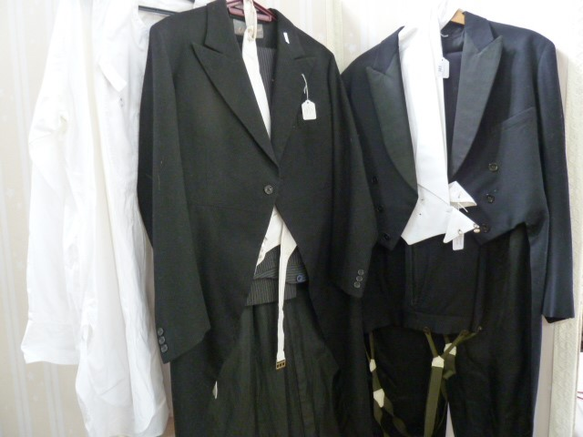 Vintage tail suit in very dark blue, with white waistcoat and trousers with braces, a black tail
