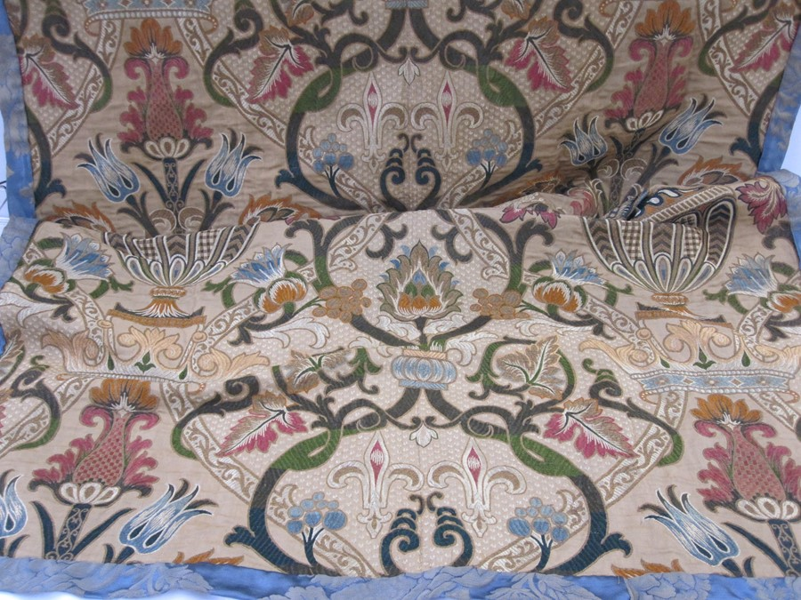 Early 20th century machine-made crewelwork-style curtain,bordered with blue damask, 180cm x 100cm