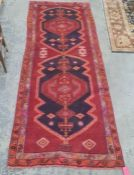 Large red ground Iranian runner, multi-coloured unique medallion design, 330 x 120cm