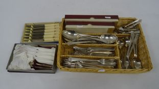 Wicker tray containing assorted plated flatware, mainly Elkington plate