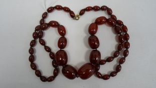 Cherry amber graduated beaded necklace, the largest bead 3cm x 2.2cm approx., the smallest 1.1cm x