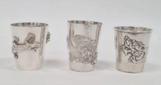 Three Chinese silver-coloured shot cups, each variously decorated with dragons or lizard and spider,