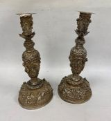 A pair of Indian/Burmese white coloured metal candlesticks, relief of warriors/hunters and