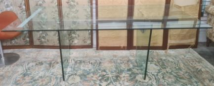 Plate glass and metal dining table, the two upright glass trestle legs united by a central metal