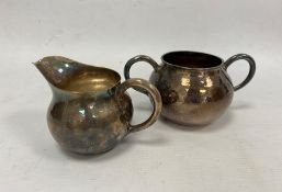 An early 20th century Japanese silver milk jug and two-handled sugar bowl, hammered detail, silver