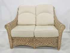 Modern conservatory-type sofa with wicker frame with cream-coloured cushions Condition