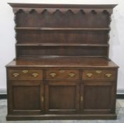 Possibly 18th century oak dresser with ogee moulded pediment above two shelves, the base of three