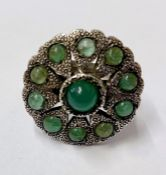 A silver coloured metal and emerald ring, possible Indian, circular/flower shaped with central