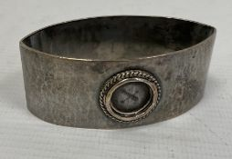 A Liberty & Co silver napkin ring, oval navette form, hammered detail (circular enamel missing),