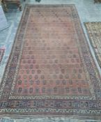 Eastern rug repeated hook medallion to a central red ground field, stepped border, 473 x 238cm