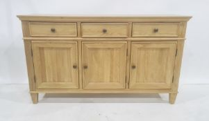 Modern oak sideboard, the rectangular top above three drawers, three cupboard doors, on square