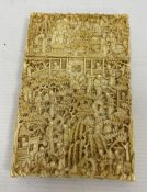 A 19th century Chinese Canton carved ivory card case, relief of figures amongst buildings and trees,