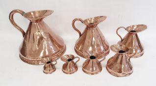 Set of seven antique graduated copper conical jug measures