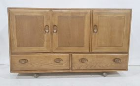 Ercol elm sideboard, the rectangular top above three cupboard doors, two drawers under, to