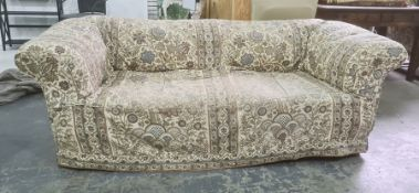 Victorian Chesterfield-type upholstered sofa with loose fitting covers, turned legs, modern roller