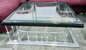 Square glass-topped coffee tableon polished metal club fender-type base
