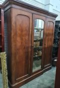 19th century mahogany wardrobe compactum, the moulded pediment with central mirrored door opening to