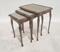 Nest of three 20th century mahogany and leather-topped coffee tables