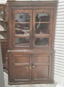20th century oak corner display unitwith two glazed doors enclosing shelves above two cupboard