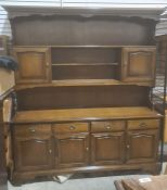 20th century dresser, the moulded cornice above assorted open shelves, cupboard doors, the base of