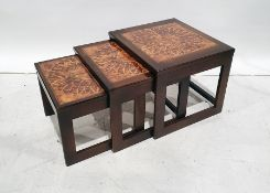 Mid-century nest of three tableswith tile tops, flowerhead design to the centre
