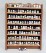 Collection of thimbleson a wooden hanging display shelf including examples by Spode, Wyeside,