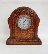 Mid 20th century Smiths oak timepiece, the arched case stylised flowerhead carved on plinth base,