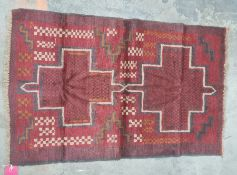 Eastern rug,red ground with two central medallions in reds, blacks, oranges and creams, 130 x 85cm