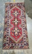 Modern Eastern-style rug, red ground with three central interlinked medallions, in creams, browns,