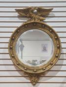 20th century circular mirrorin gilt-effect frame surmounted by eagle, 68cm x 45.5cm