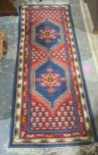 Modern Eastern-style runner with two central medallions on a red ground, stepped border, 210cm x