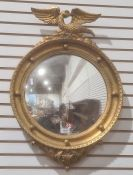 Modern convex wall mirrorwith gilt-effect finish, surmounted by eagle