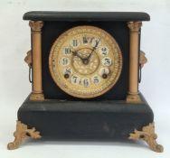 Mantel clock with arabic numerals, painted black body and gold painted highlights, chiming