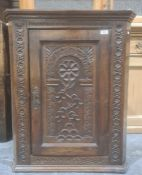 Probably 18th century wall-hanging corner cupboardwith carved decoration to the door, 83cm high