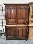 Georgian oak cupboard, the moulded cornice above panelled doors enclosing shelves, the base of two