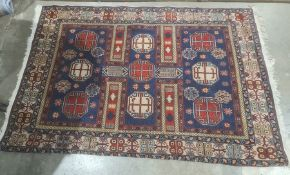 Modern Eastern-style blue ground rug in blues, reds, creams and yellows, 196cm x 135cm