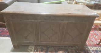 Possibly 18th century and later oak coffer, the rectangular top with moulded edge, three carved