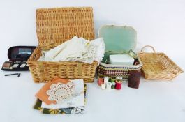 Wicker picnic basketfilled with assorted linens and textiles, table ware, another basket, a