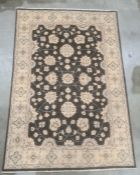 Modern Eastern-style black ground rug, the central field with foliate decoration, on a cream