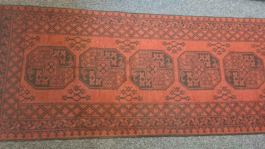 Modern Eastern-style red ground runnerwith repeating central medallions in reds and blacks, 387cm x