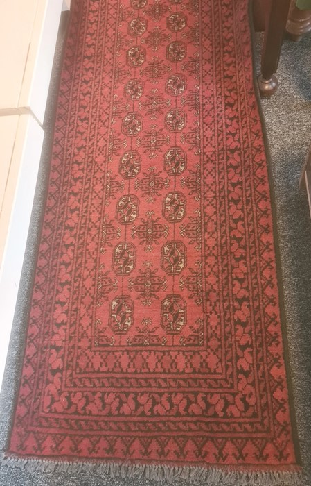 Modern red ground rugwith repeating central medallions, in reds, blacks and whites, 296cm x 80cm